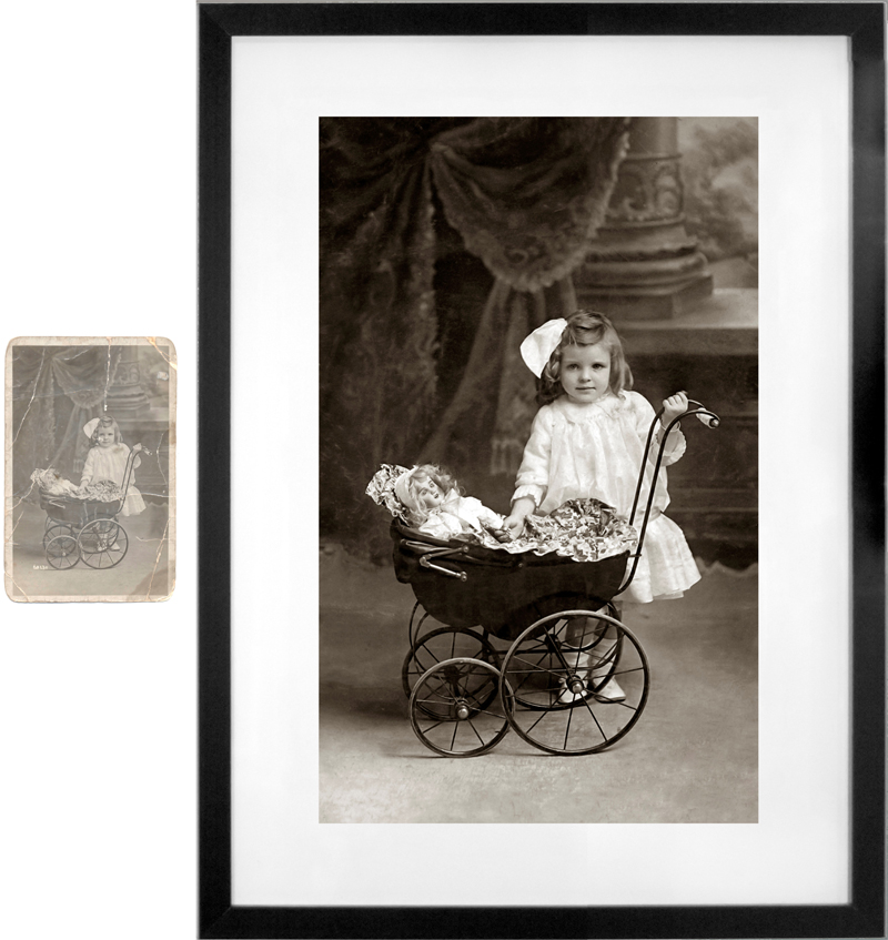 restored old black and white photograph, girl with a doll in a pram