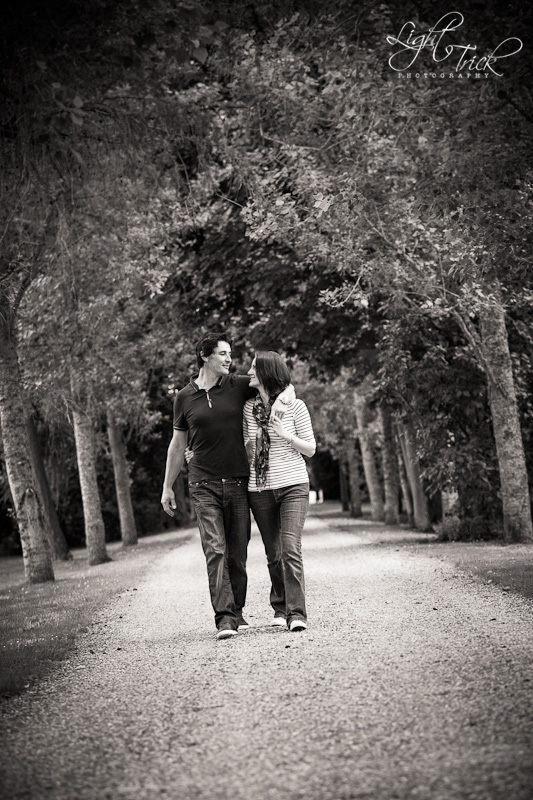 engaged couple walking an avenue of trees