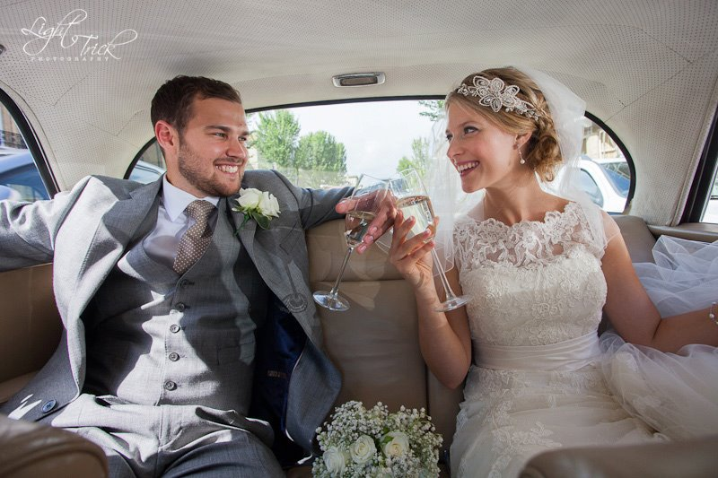 beautiful wedding couple inside wedding car with champagne glasses