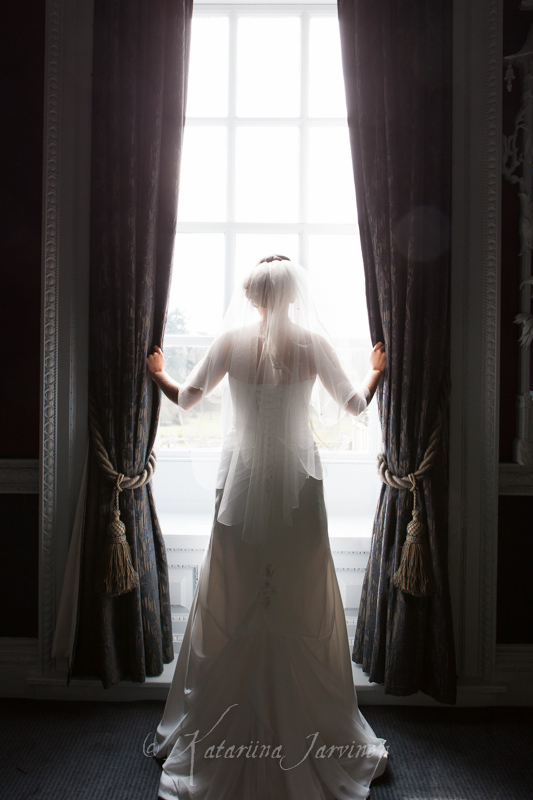 Bride looking out of window at Buxted park wedding venue