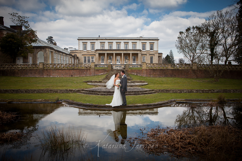 wedding couple posing in front of the pond at Buxted Park hotel, East Sussex