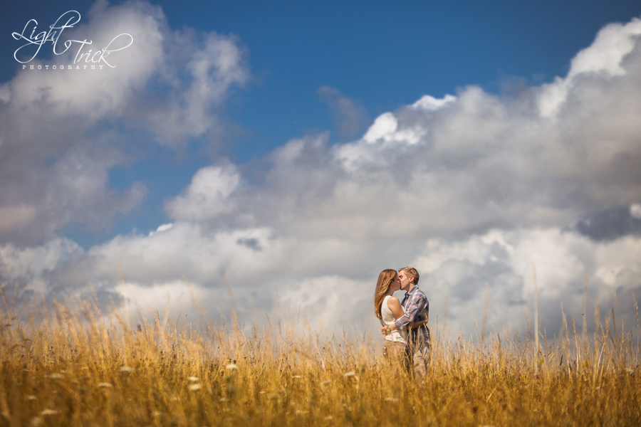 engagement shoot - beautiful couple kissing in a grass field