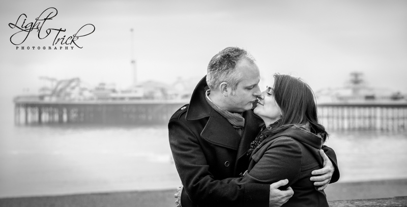 couple kissing with Brighton Pier in the background