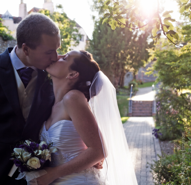 wedding couple kiss backlit into sun