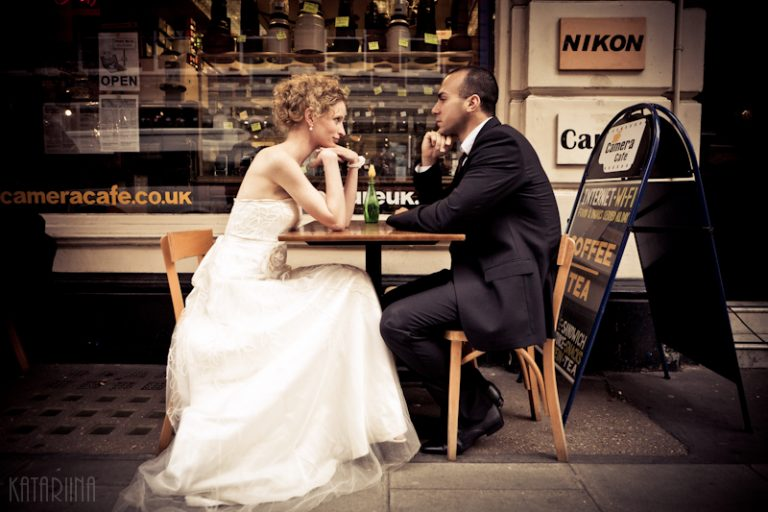 wedding couple sitting at a table in front of camera shop