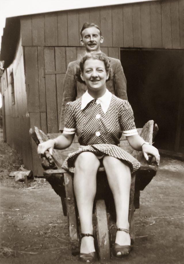 husband pushing wife in a wheelbarrow, old photograph restored