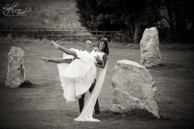 groom lifting bride in a stone circle
