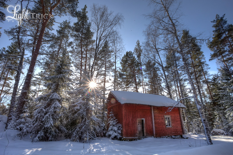 wooden red shed in the winter with snow and woods