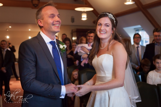 happy smiling couple exchange rings